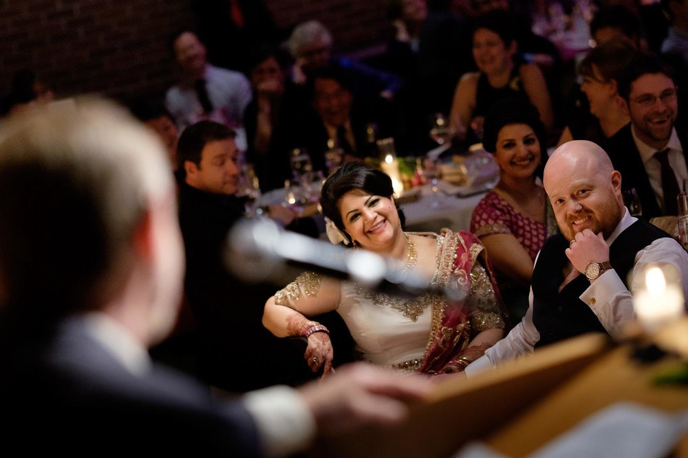 the bride and groom listen to a speech during their wedding reception at the Toronto Reference Library.
