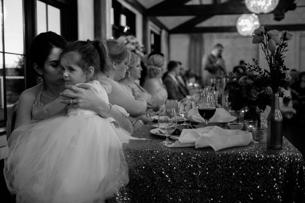 the flower girl is comforted by her mother during the wedding reception at WhisteBear golf course in Cambridge, Ontario.