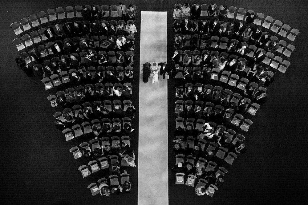 An overhead black and white wedding photograph of a bride walking down the aisle with her parents during her jewish wedding ceremony at the Toronto Reference Library.