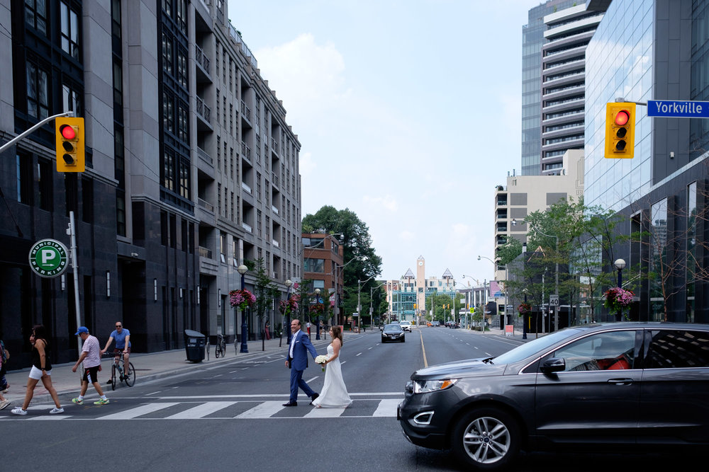 Bride and groom cross a busy Toronto intersection while having wedding portraits taken in Toronto's Yorkville neighbourhood.