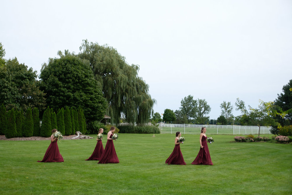 The bridesmaids walk to the outdoor wedding ceremony at the Hessenland Inn in Southwestern Ontario.