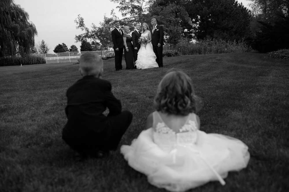 The ring bearer and flower girl watch during family portraits at Alex and Colton's wedding at the Hessenland Inn in Ontario.
