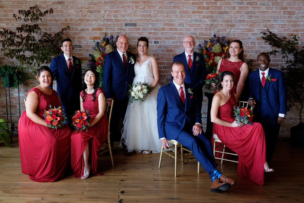 Stephen + Coral pose for a formal portrait with their wedding party at the Dominion Telegraph Event Centre in Paris, Ontario.