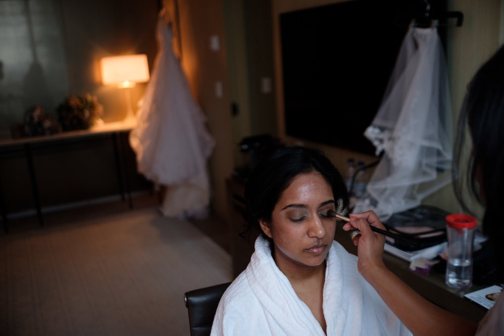The bride has her makeup done in her suite at the Toronto Four Seasons hotel before her new years eve wedding at the Toronto Reference Library Appel Salon.