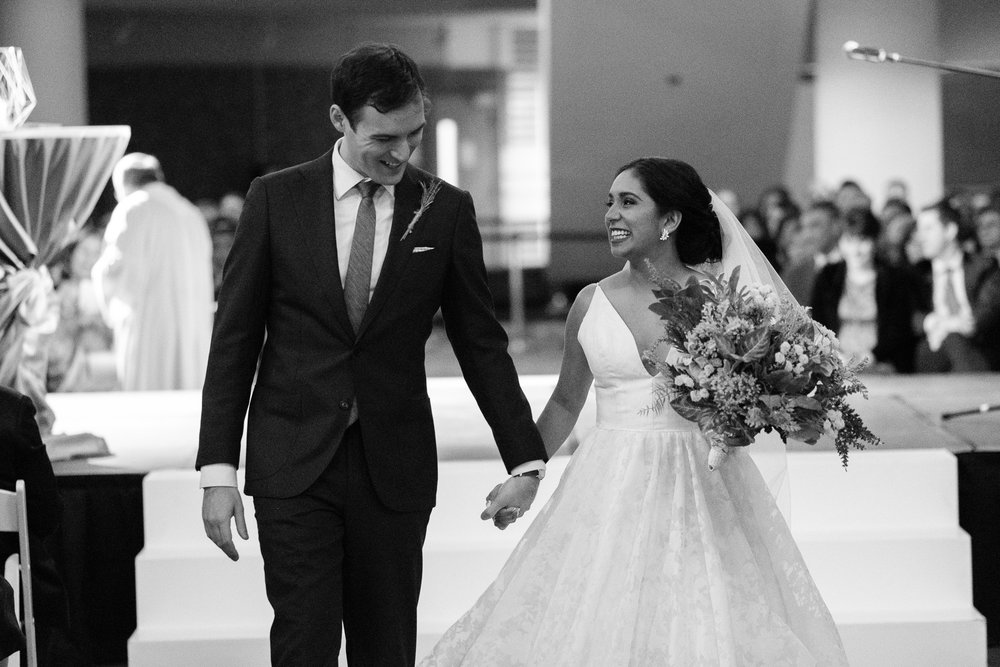 Andrea + Rob share a moment as they walk down the aisle as husband and wife after their new years eve wedding ceremony at the Toronto Reference Library