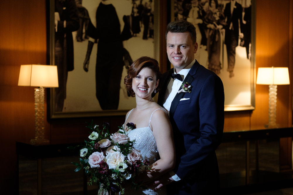 the bride and groom pose for a romantic portrait in the lobby of the King Edward Hotel in Toronto before their winter wedding at the Enoch Turner Schoolhouse.