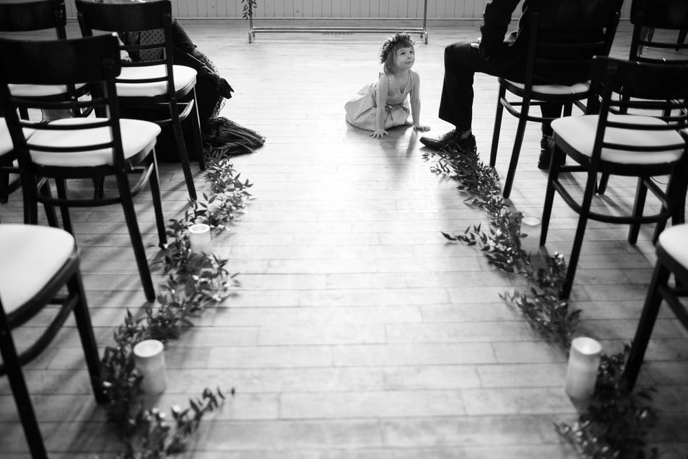 The flower girl hangs out in wedding aisle before the winter wedding ceremony at the Enoch Turner Schoolhouse in Toronto.