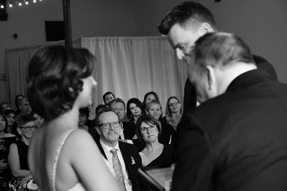 The brides parents look on during the wedding ceremony as the bride and groom exchange vows at the Enoch Turner Schoolhouse in Toronto.