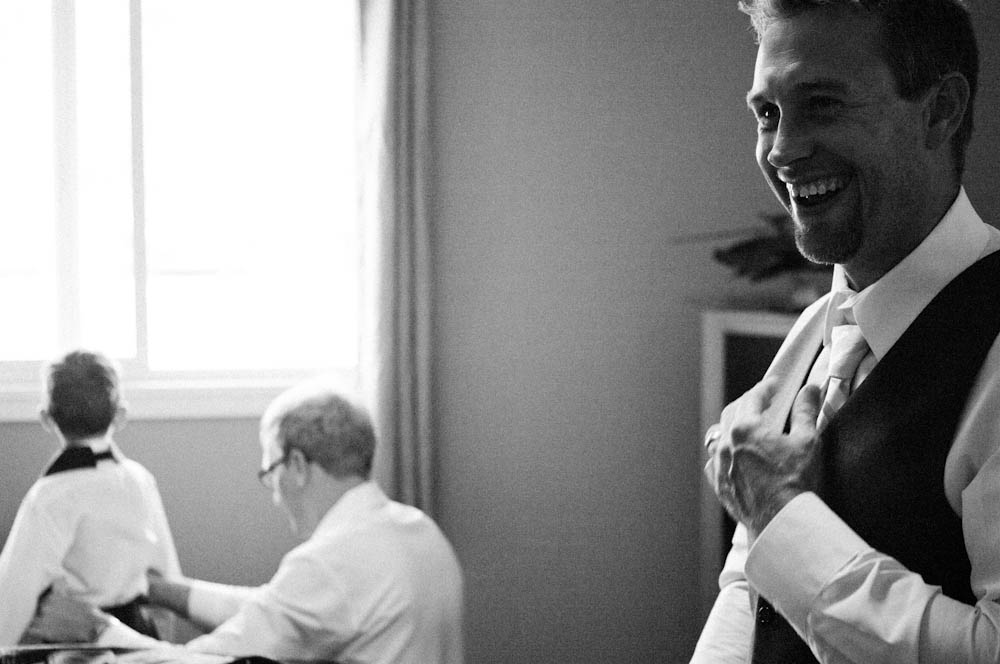 One of the groomsmen cracks a smile while the best man helps the ring-bearer get dressed.
