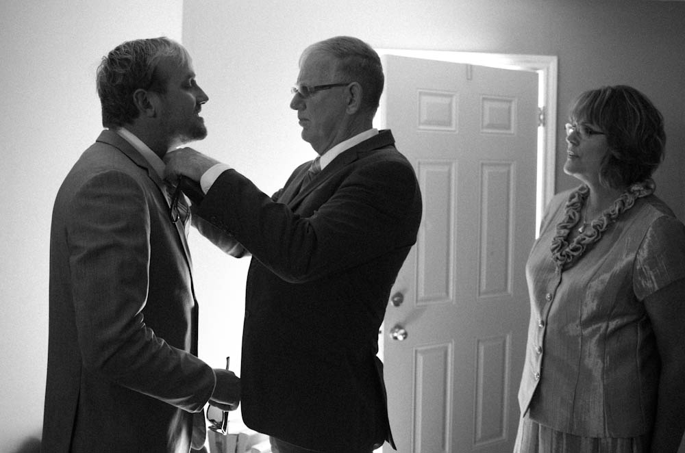 Father of the groom helping the groom with last minute tie preparations.