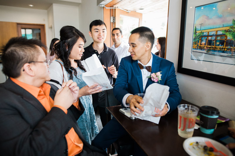 """Even when big """"things"""" aren't happening on a wedding day, I love to photograph the in-between moments like this. Here, a few friends of Jesse and Patricia bring donuts from 49th and Parallel to munch on while they rest at JJ Bean (so much """"Main Street"""" going on in that sentence!!)."""