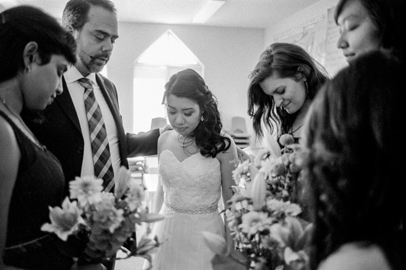 The bride prays with the bridesmaids and her pastor before heading down to the ceremony.