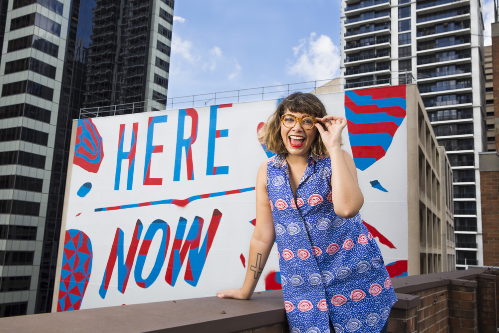 Jess Scully in front of Elliot Numskull's 'Here, Now' mural for Art & About Sydney
