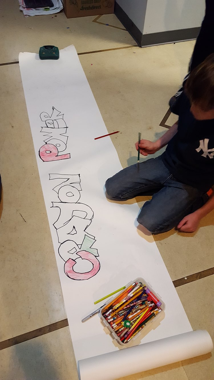 A student sketching a Crayon Power banner