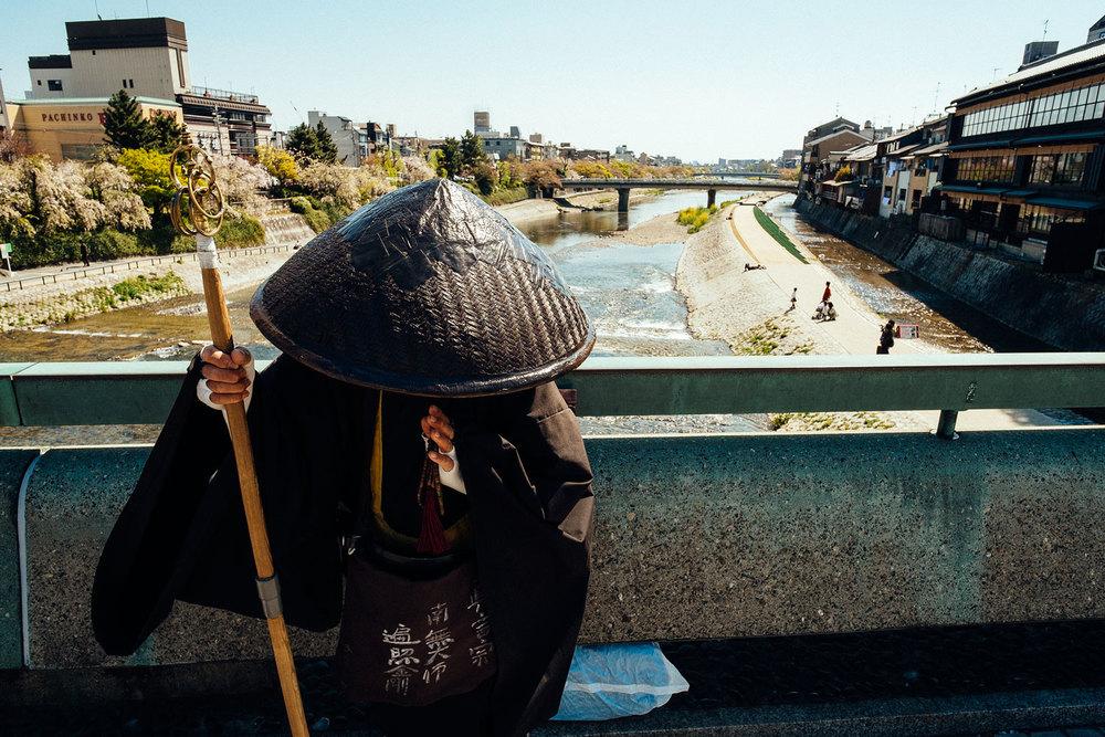 Un monaco intento a pregare su uno dei ponti di Kyoto.