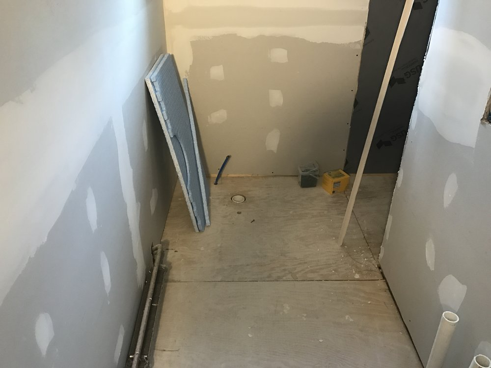 Direct nail hardwood flooring was removed during this Olyphant bathroom remodel. Type BC plywood was installed to provide a stable subfloor for the tile installation
