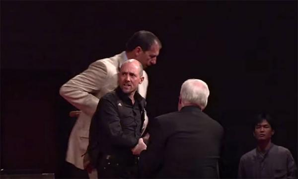 Young prophet being swiftly escorted out of John MacArthur's pulpit and out of the church.