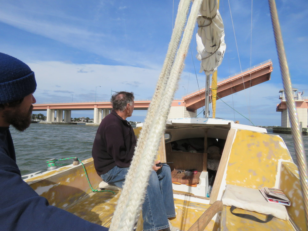 "Rick Lanigan & Brody Lanigan (steering) waiting for the bridge to open. Taking ""Religion"" to the boat yard.  Northern winds-unable to sail. Motored from New Symrna Beach to Port Orange, FL. 01/2015"