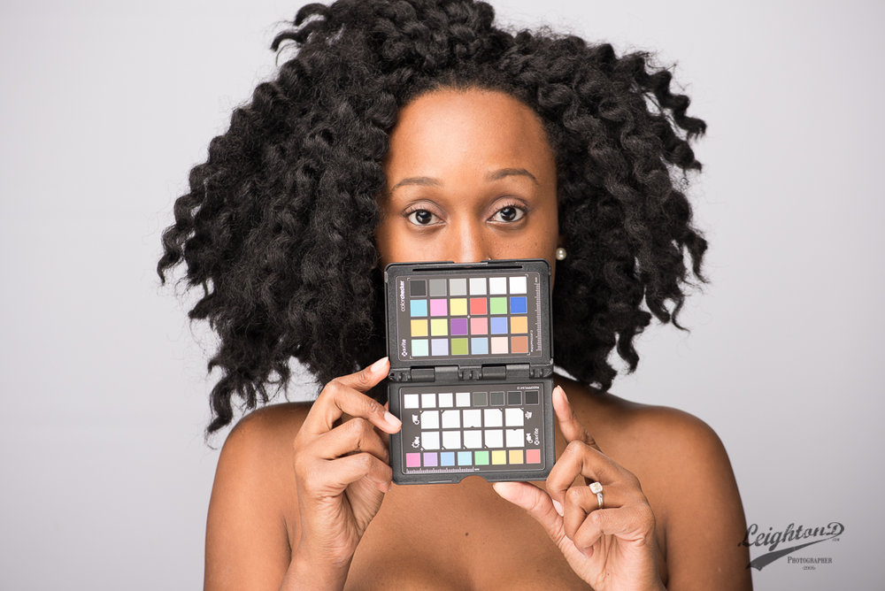 Unedited: Model, Aquisha G. holds up a color checker for establishing a color reference.