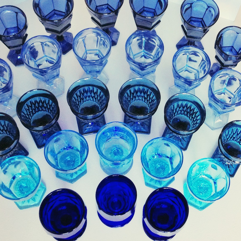 A spectrum of vintage blue goblets ready to go to an outdoor dinner.