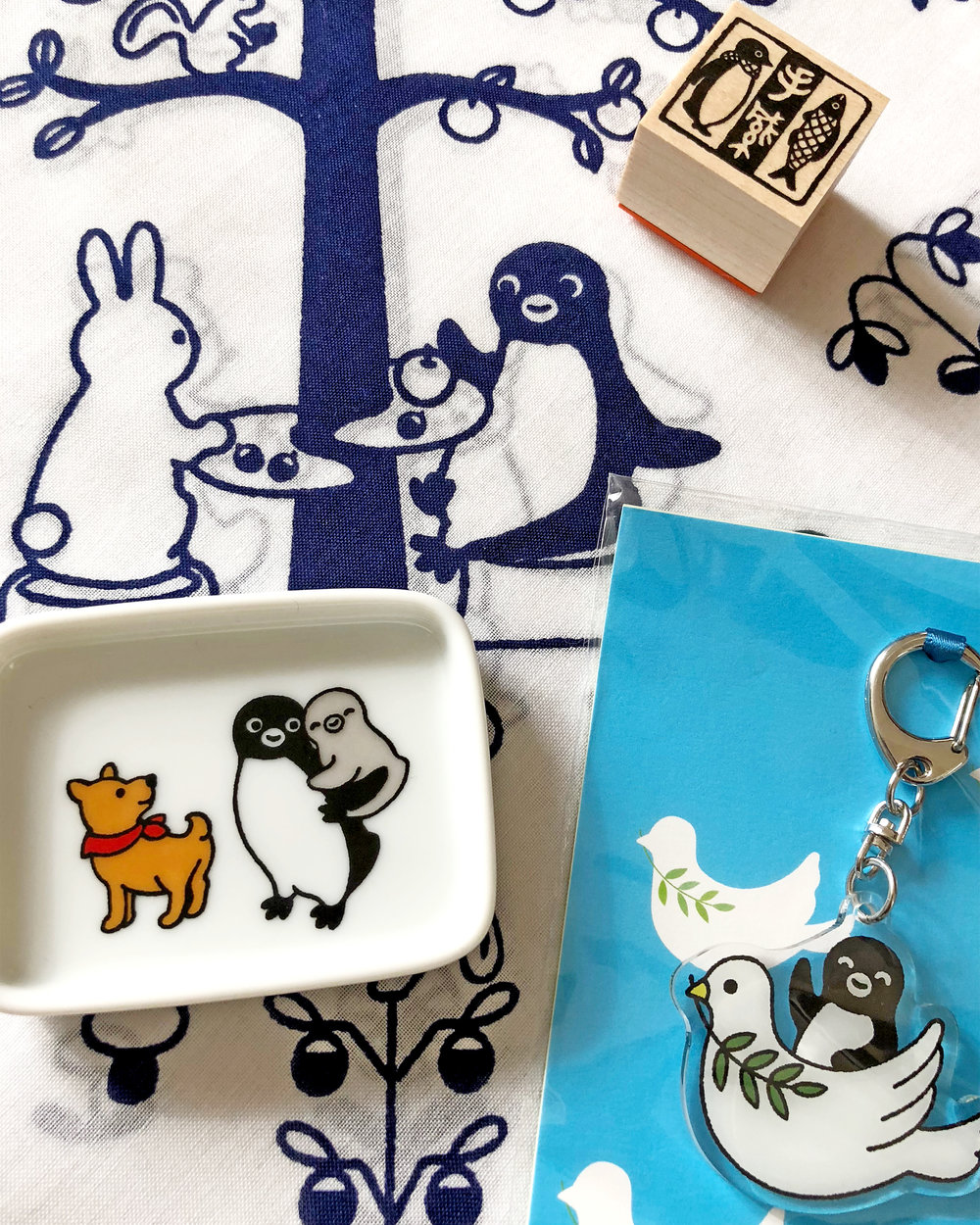 Suica products: stamp, small ceramic dish, keychain, and furoshiki wrapping