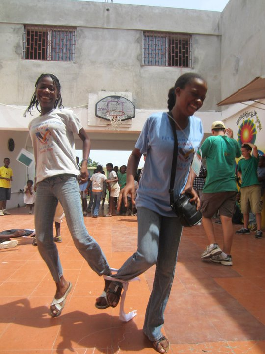 Two girls having fun with the three-legged race at Fet Bondye Bo Lanme 2011.     The key to the three legged race is moving forward with the same pace and as though the two legs tied together are actually one.  This provides a great metaphor for the relationship between HTF and our partners.