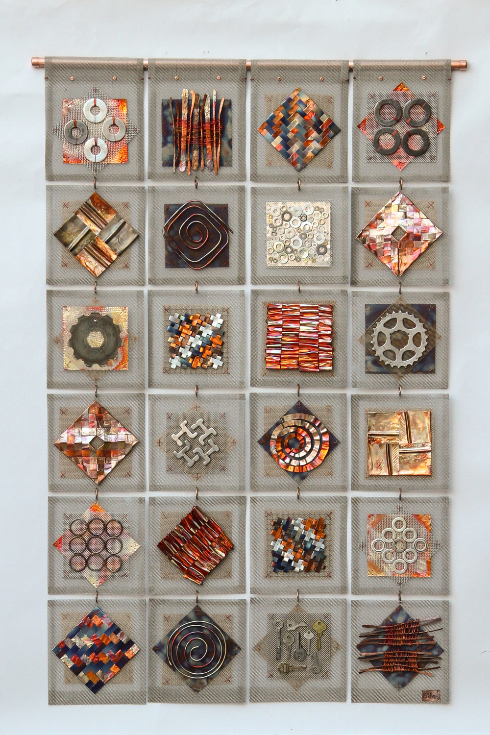 Scrapyard Quilt.24 panels of stainless mesh, onto which are stitched elements using copper wire, copper strip, brass, washers, industrial  scrap, bike parts. 74x118cm/29x 46""