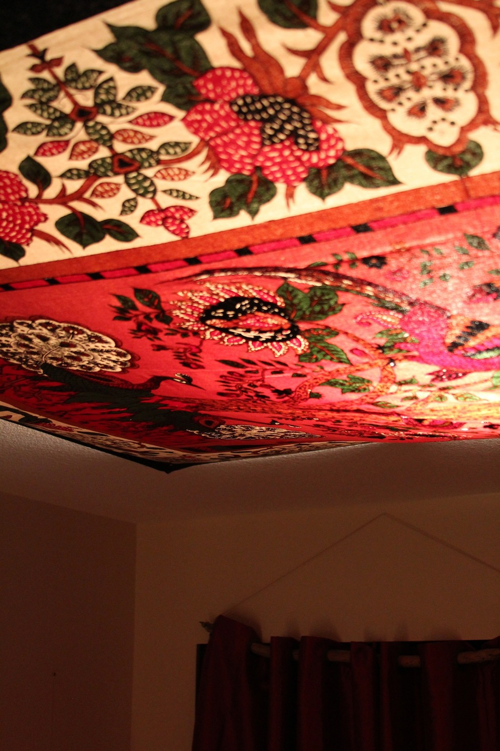 A tree of life tapestry hangs over a too-bright-on-it's-own-light, creating a warm + soft, red glow