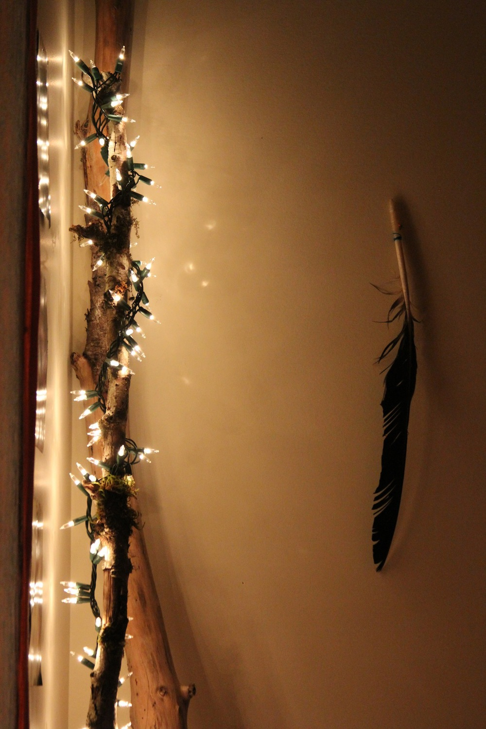 An eagle feather hangs beside a DIY lamp - twinkling lights wrapped around a long piece of wood!