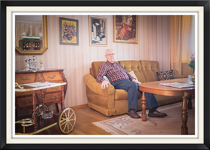 Grandpa  H enry, pay attention to the handmade wooden ship in the mirror, newspaper on the table and his favourit couch.