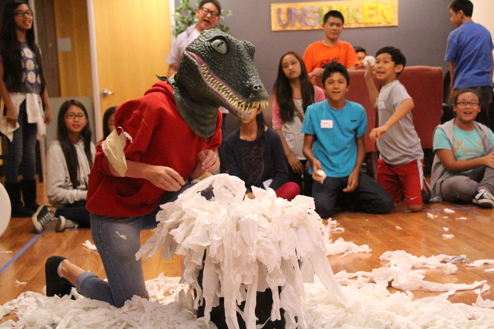 And of course, our game masters were genius enough to invent a game that involved cleaning up too! Students donned dinosaur masks and competed to see which team could pick up the most toilet paper with their wrists bound together by masking tape. It was surprisingly challenging, and makes me wonder how T-rexes could become predators when they couldn't even pick things up.