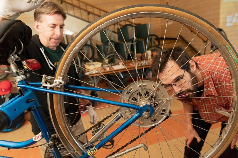 Joel (right) fixing a bike at a Repair Cafe.
