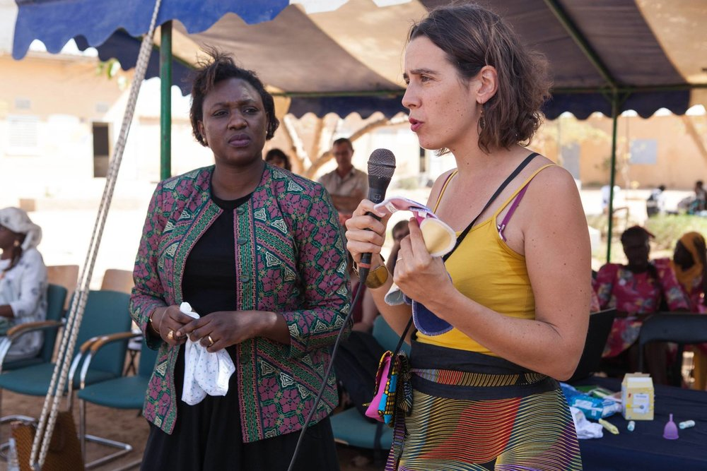 "Selly Ba (left), a gender specialist with Speak Up Africa, and Marina Gning (right), CEO of Apiafrique, demonstrate how to use feminine hygiene products, including a reusable sanitary pad manufactured by Apiafrique, during a menstrual hygiene management (MHM) workshop at a high school in Ngaparou, Senegal. Conducted in partnership with Speak Up Africa and Apiafrique, the workshop is part of the ""No Taboo Periods"" campaign that advocates for improving practices around menstrual hygiene within communities."