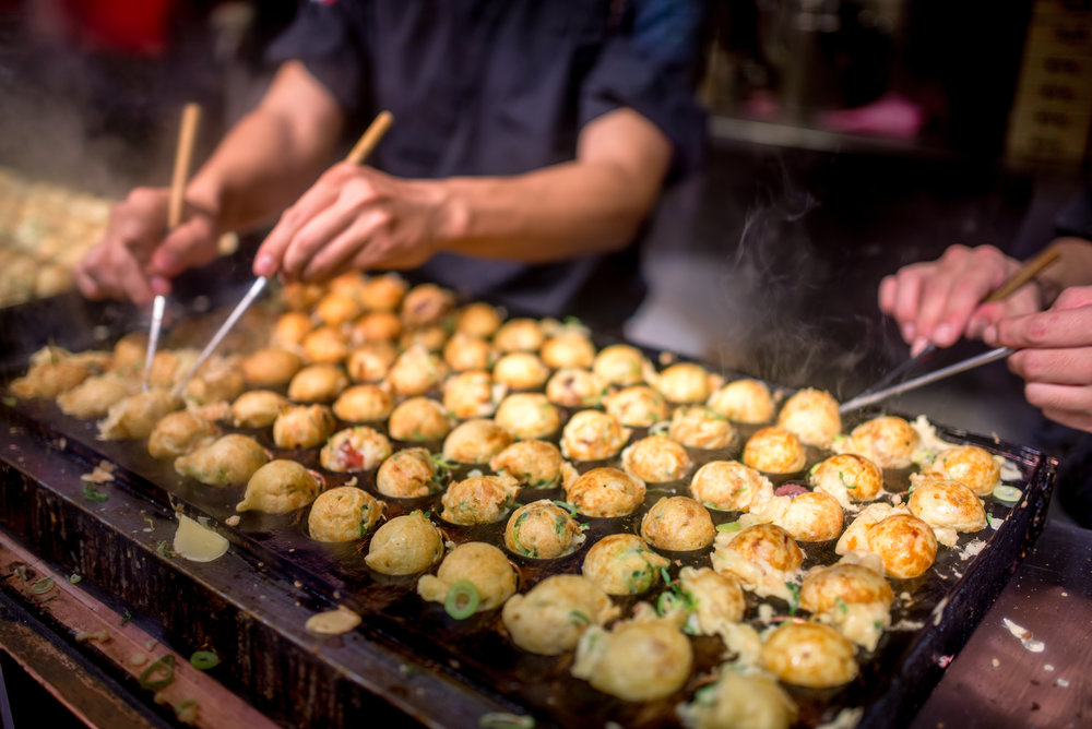 Takoyaki - a Kansai (Western Japan) favorite- savory balls of delicious, piping hot batter - being made on the grill.