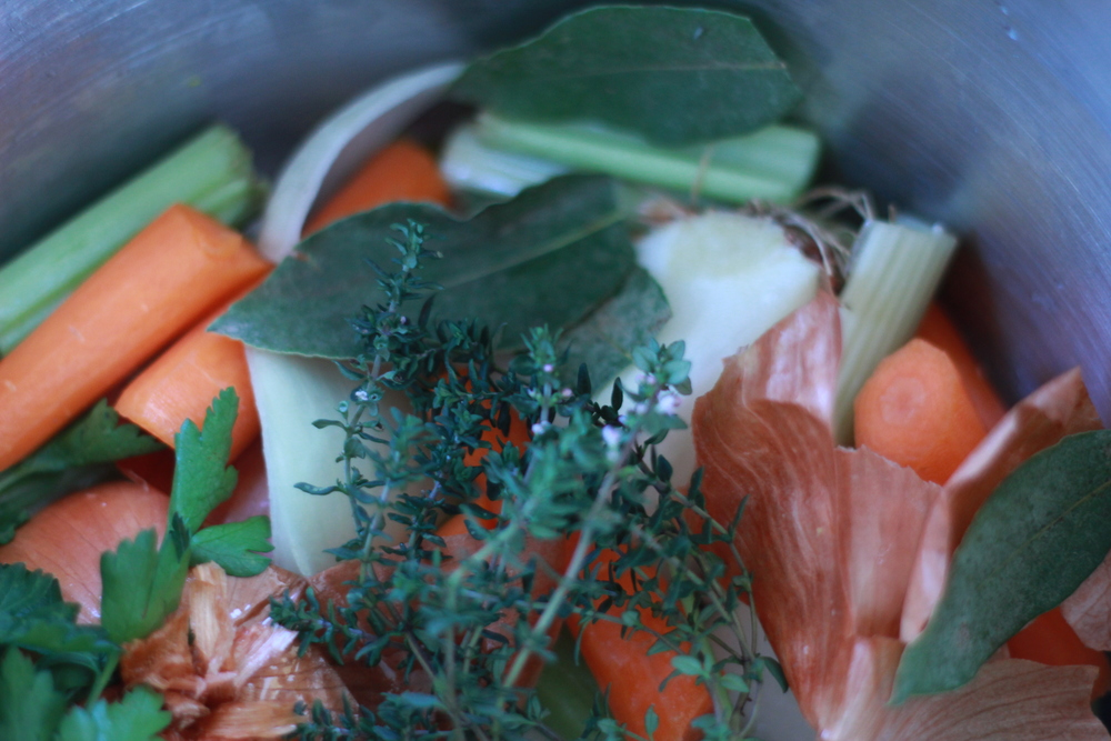 Some ingredients for chicken broth: carrot, onion, celery, garlic, thyme, bay leaves, parsley.