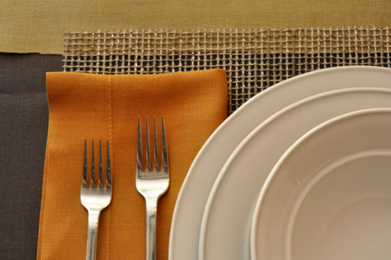 The Setting: Chilewich mat, Libeco Vence gold linen napkin, David Mellor Classic flatware, and Simon Pearce Cavendish dinnerware