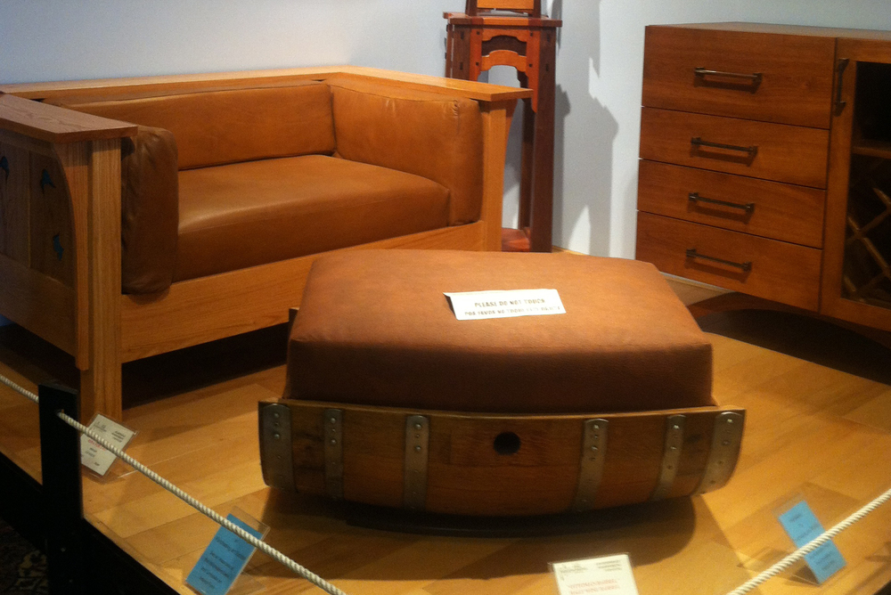 Pictured in front is an ottoman + coffee table + storage cask designed by Roberto Mendez,