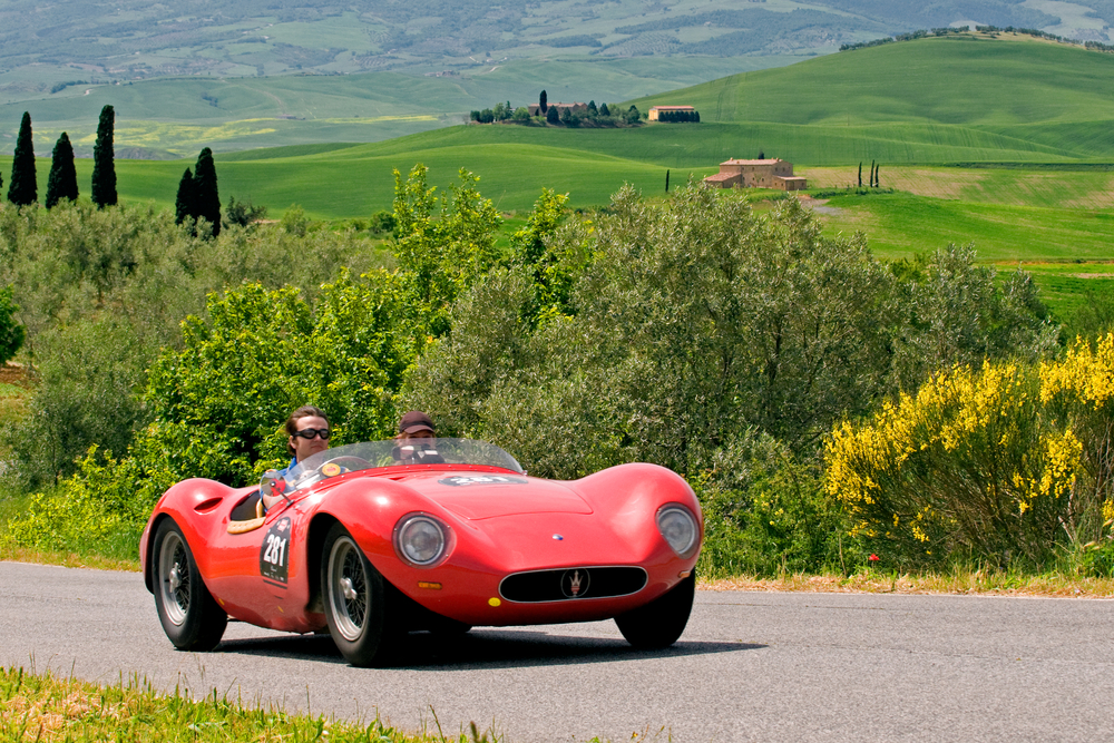 Participants in the Mille Miglia make their way through Val D'Orcia in Tuscany