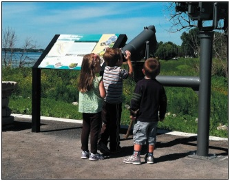 Young nature enthusiasts enjoying the view of the restored coastal wetland and its wildlife.
