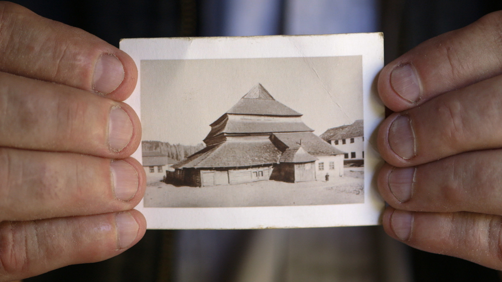 Still 1: Rick Brown holds the photo of Gwozdziec Synagogue that inspired them to reconstruct it.