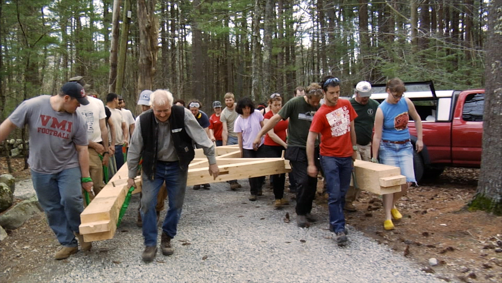 Still 8:  Rick Brown leads a group of timber framers (students and professionals) to the final site of the Polish bell tower.