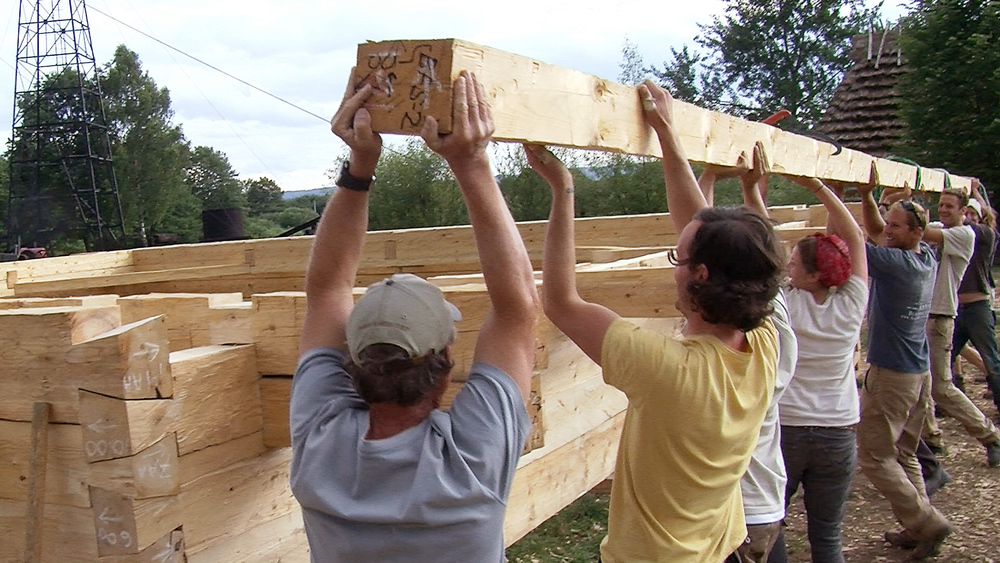 Still 15: At the Sanok workshop in 2011, students and professionals lift a dimensional timber on to the log wall.