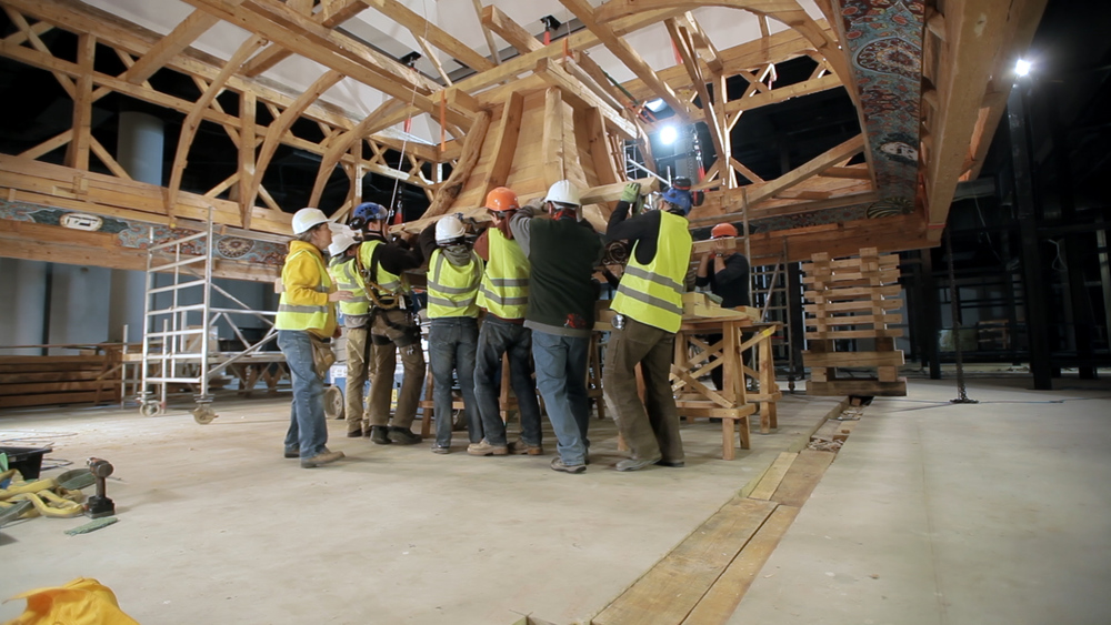 Still 40:  The timber frame crew lift the lantern onto a platform before hoisting it into place in the roof.