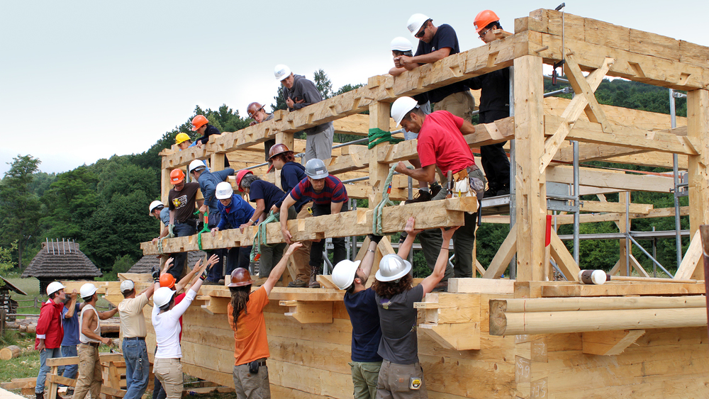 In Sanok, Poland, timber framers and students on the ground level using teamwork and collective human power to lift a finished log to a receiving team on the roof structure.
