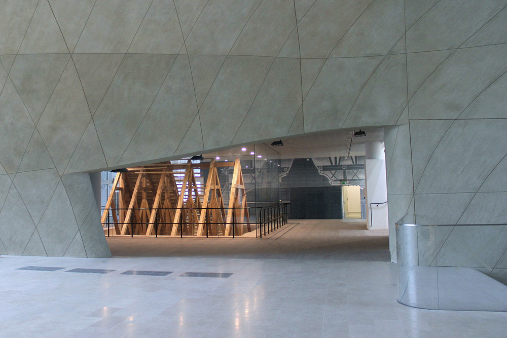 View of the Gwozdziec timber frame in the POLIN Museum in Watsaw, Poland.  The roof rises up through the first floor from the lower level of the museum.