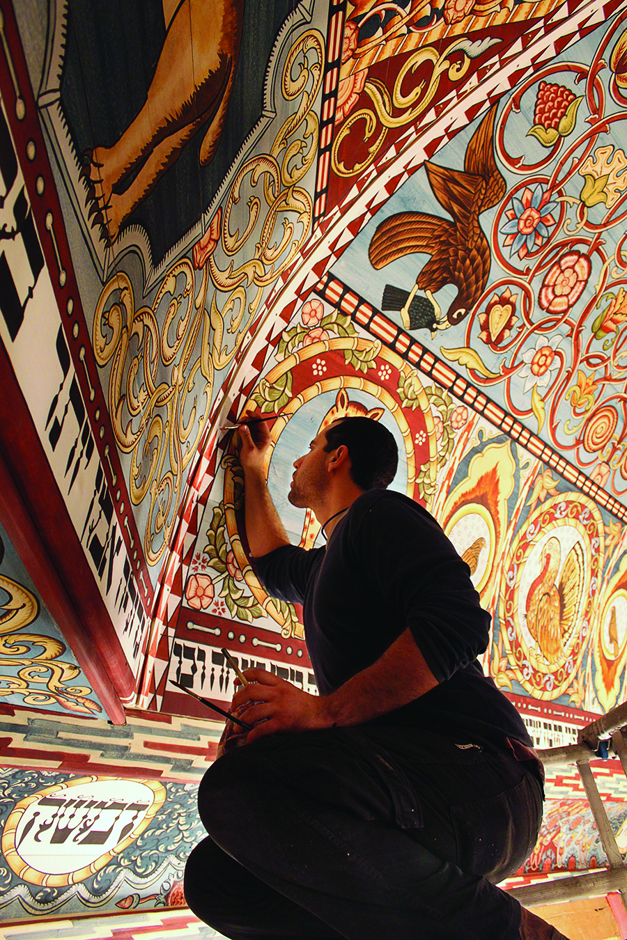 Jason Loik, painting leader, puts finishing touches on the Gwozdziec synagogue ceiling.