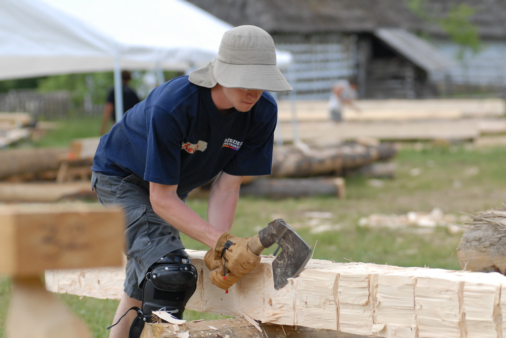 Mastering the method of medieval hand hewing,  student Kevin Klein shapes a log into dimensional timber.