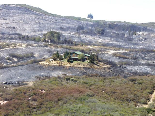 Home surrounded by wildland that survived a fire due to good defensible space. Source: 2010 Strategic Fire Plan for California, April 2016