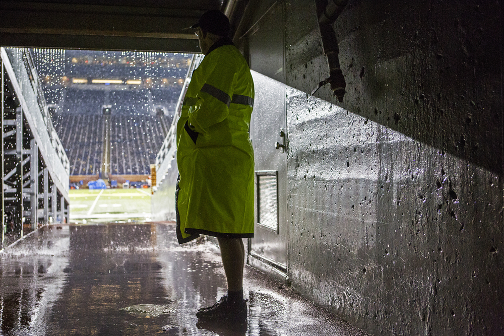 A University of Michigan Stadium official waits for a 2 hour and 24 minute rain delay to end during the Michigan versus Utah game in the Big House on October 20, 2014.