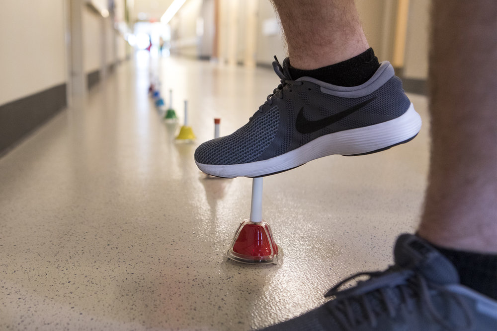 Connor Walker lifts his feet to touch the top of a bell during a music therapy session at Spaulding Rehabilitation Hospital in Charlestown on Oct. 24, 2018. Despite not having sensation in his legs, Walker took his first steps during an earlier music therapy session.